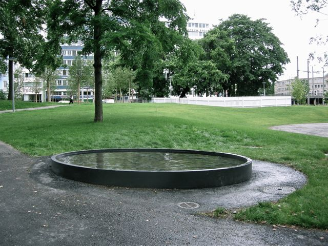 Fountain with relief in concrete, 2008. In the background the Installation 'Landler/Polka, Erich Steinbrecher. Basel, Elisabethenpark